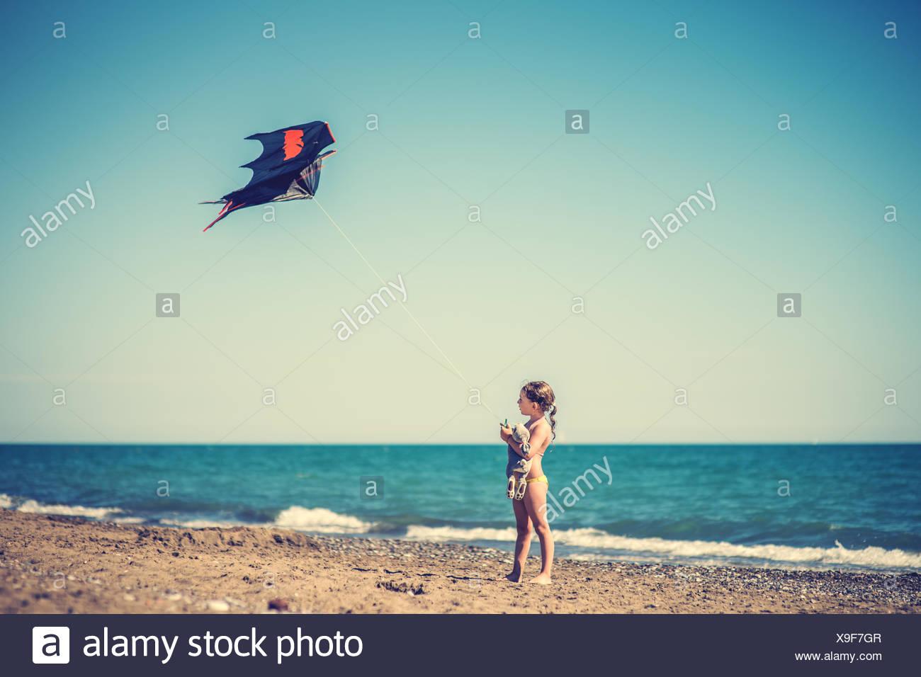 Mädchen, die Drachen am Sandstrand Stockbild
