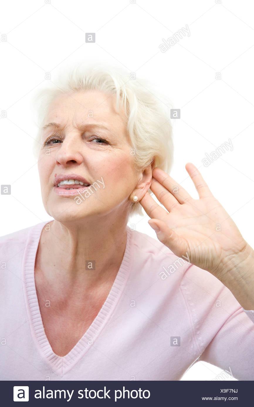 Alte Frau nicht etwas hören, legt Hand hinter dem Ohr Stockbild