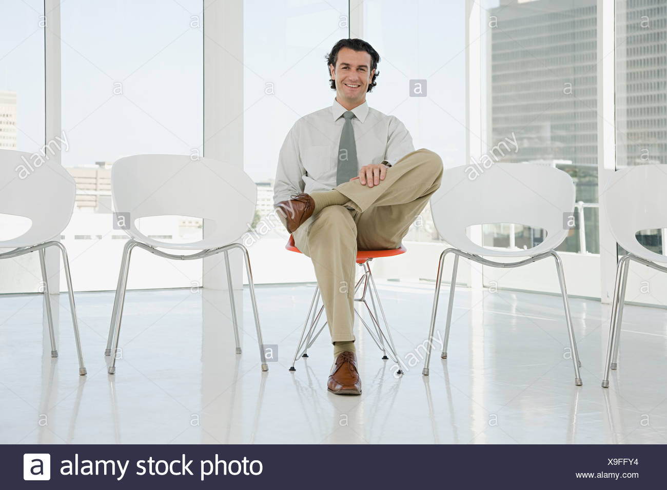 Mann sitzt im Stuhl Stockbild