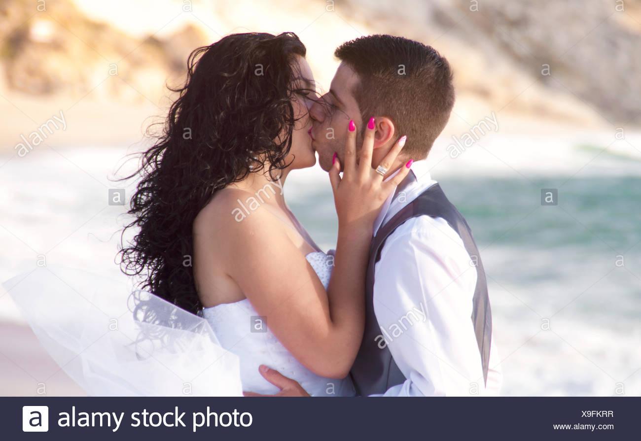 Bräutigam seine Braut am Strand küssen Stockbild