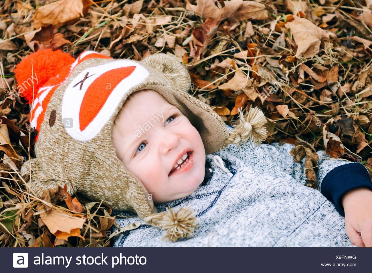 Junge liegend in Haufen von Blättern Stockbild