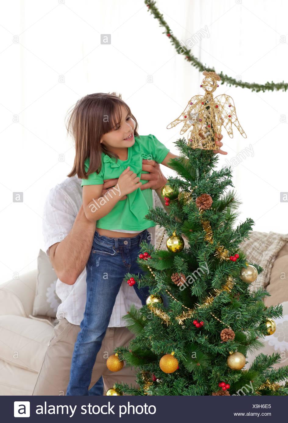 Aufmerksamen Vater hält ihre Tochter um den Weihnachtsbaum schmücken Stockfoto