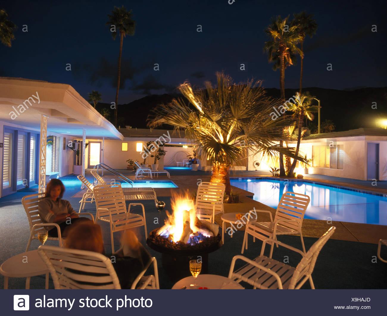 Zwei Frauen sitzen Feuerstelle auf Terrasse neben Schwimmbad des ...