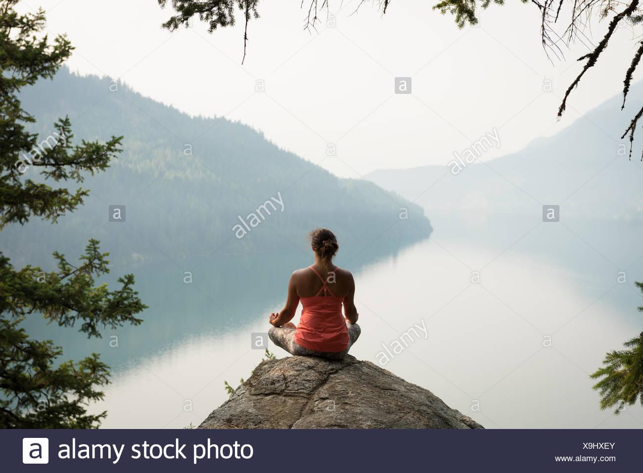 Passende Frau in Meditation Haltung auf dem Rand von einem Felsen sitzend Stockbild