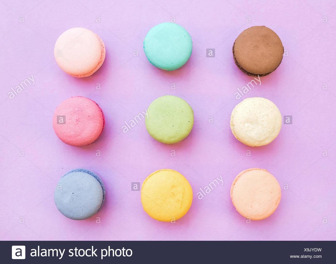 Süße bunte französische Macaron Kekse auf Pastell rosa Hintergrund, Ansicht von oben Stockbild