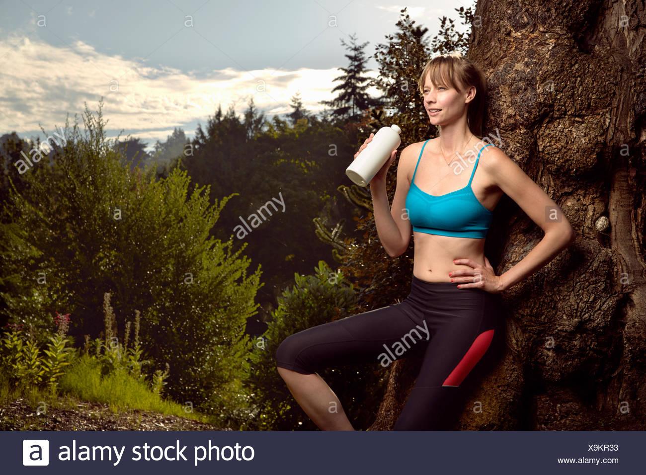 Weibliche Läufer gelehnt Rock im Park-Trinkwasser Stockbild