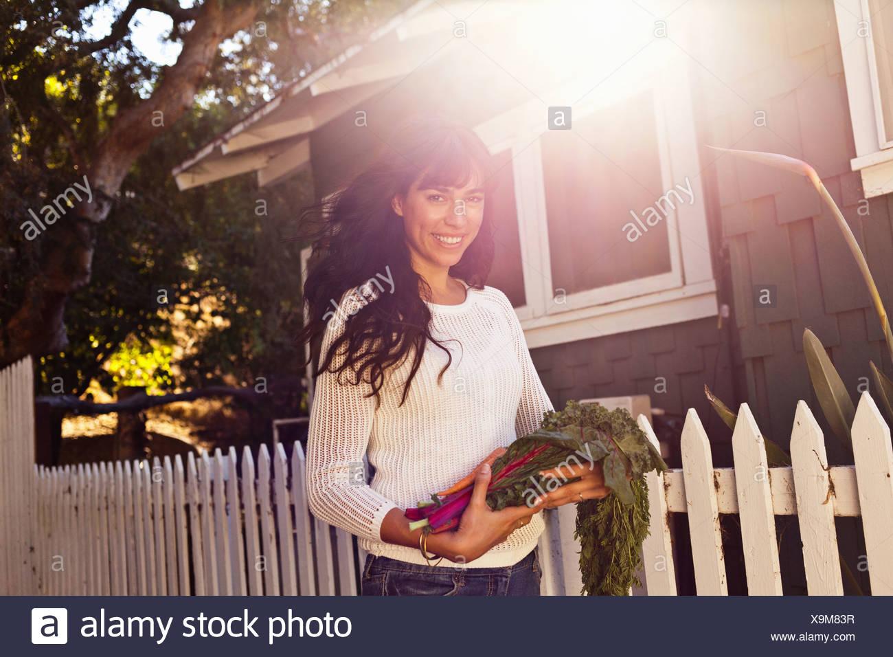 Porträt der jungen Frau hält einheimische Gemüse Stockbild