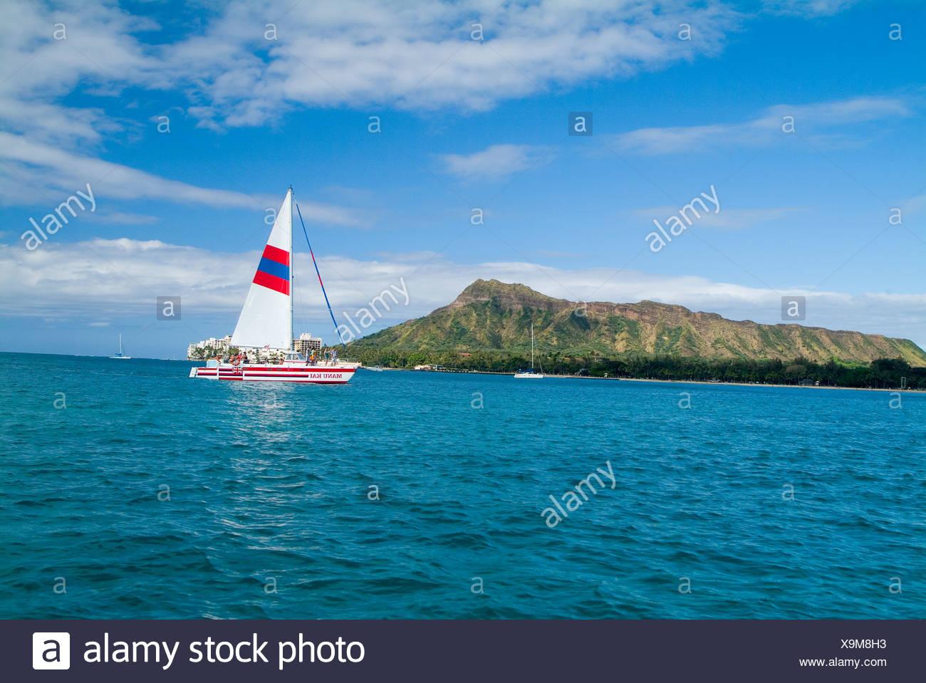 Totale des Diamond Head von einem Segelboot aus Waikiki mit einem Katamaran Sport eine weiße gestreifte Segel im Vordergrund. Stockbild