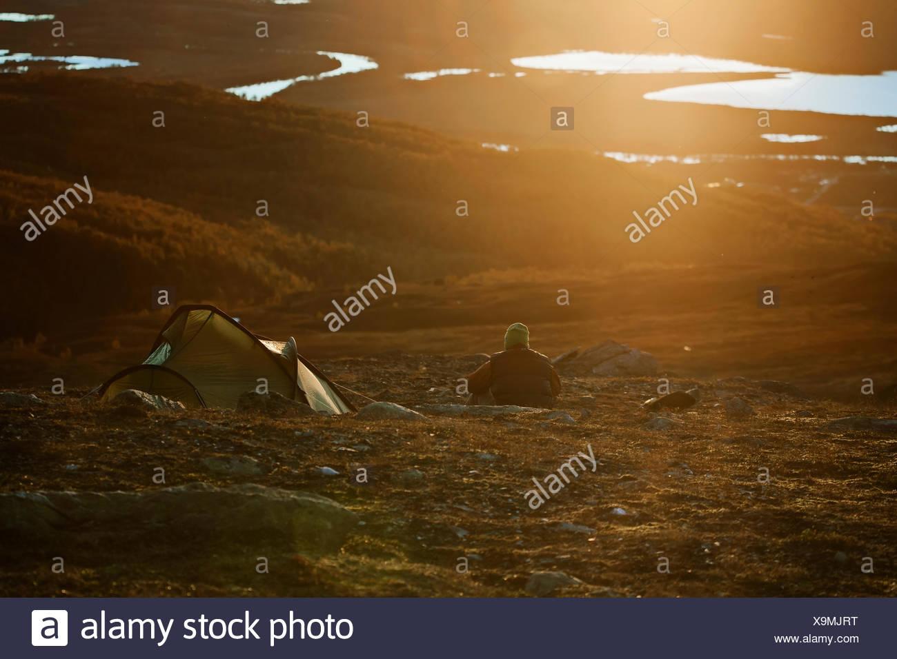 Schweden, Vasterbotten, Hemavan, Mann camping bei Sonnenuntergang Stockbild