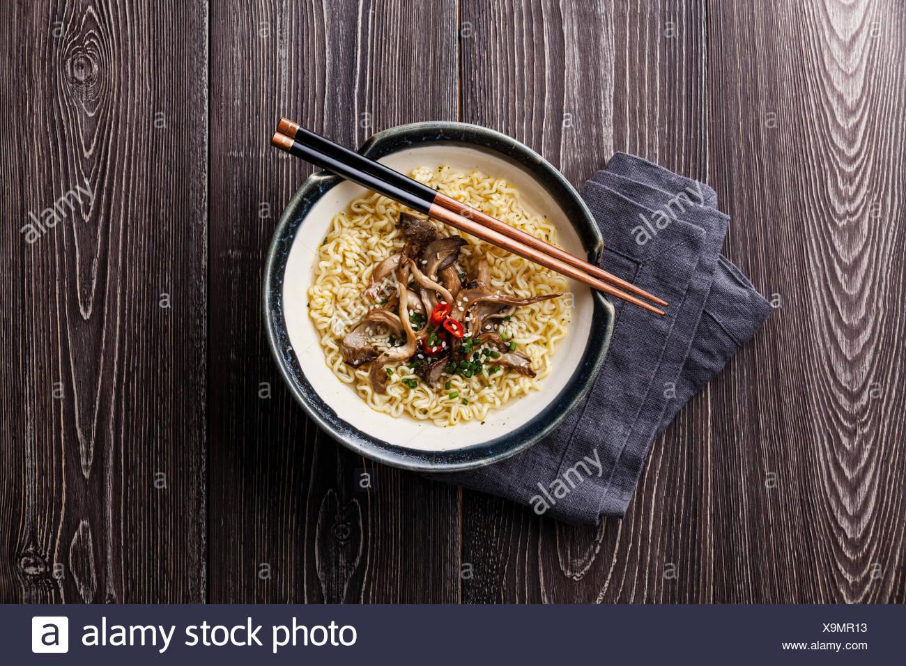 Asiatische Nudeln mit Austernpilzen in Schüssel auf grauem Hintergrund aus Holz Stockbild