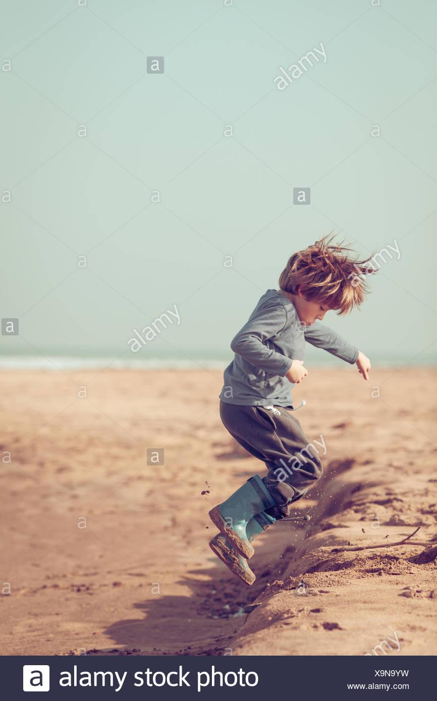Junge springt in den Sand am Strand, Marokko Stockbild