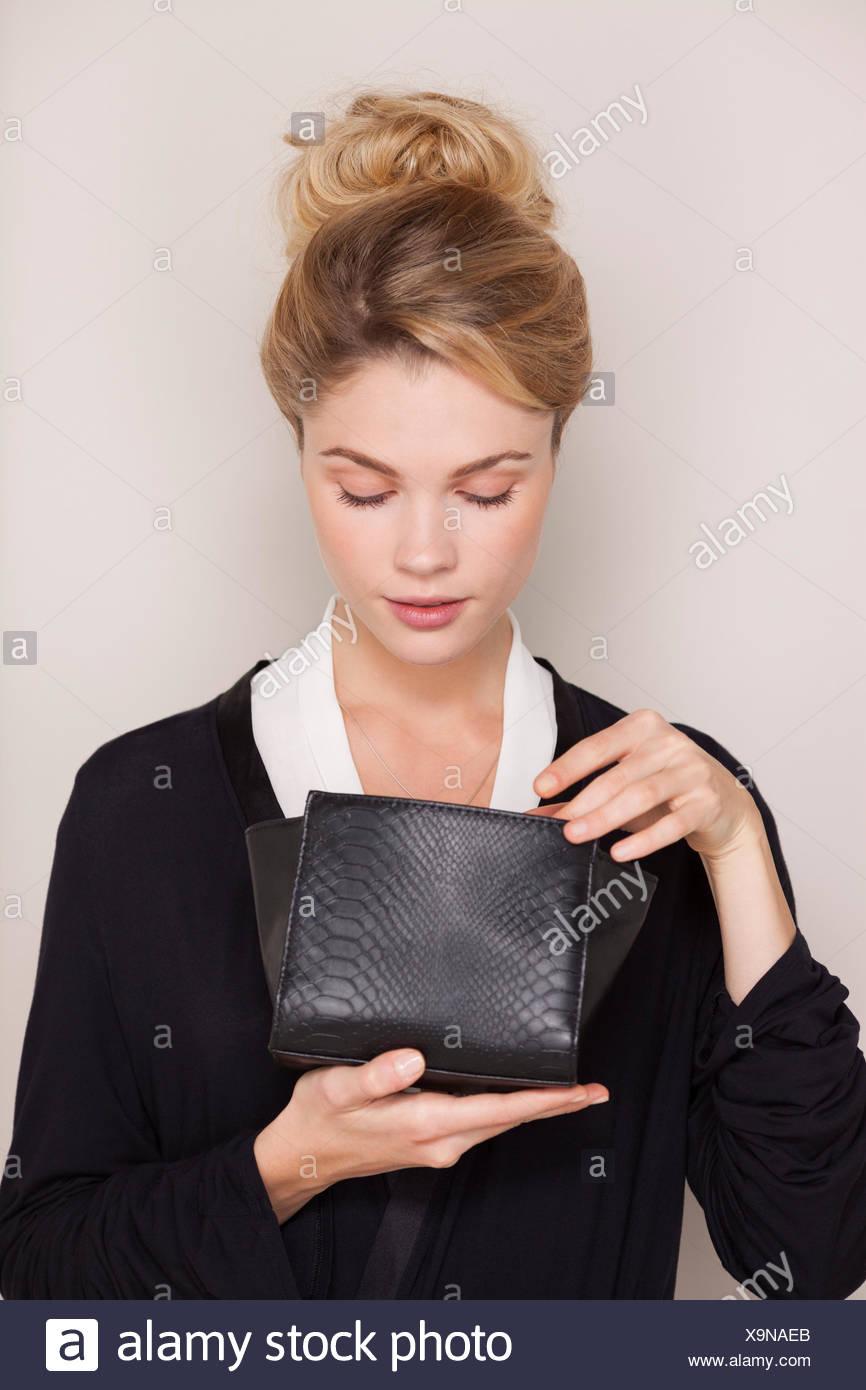 Schöne Frau, die Überprüfung ihrer Kosmetiktasche Stockbild