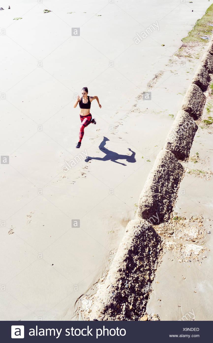 Junge Frau Strand entlang läuft, Erhöhte Ansicht Stockbild