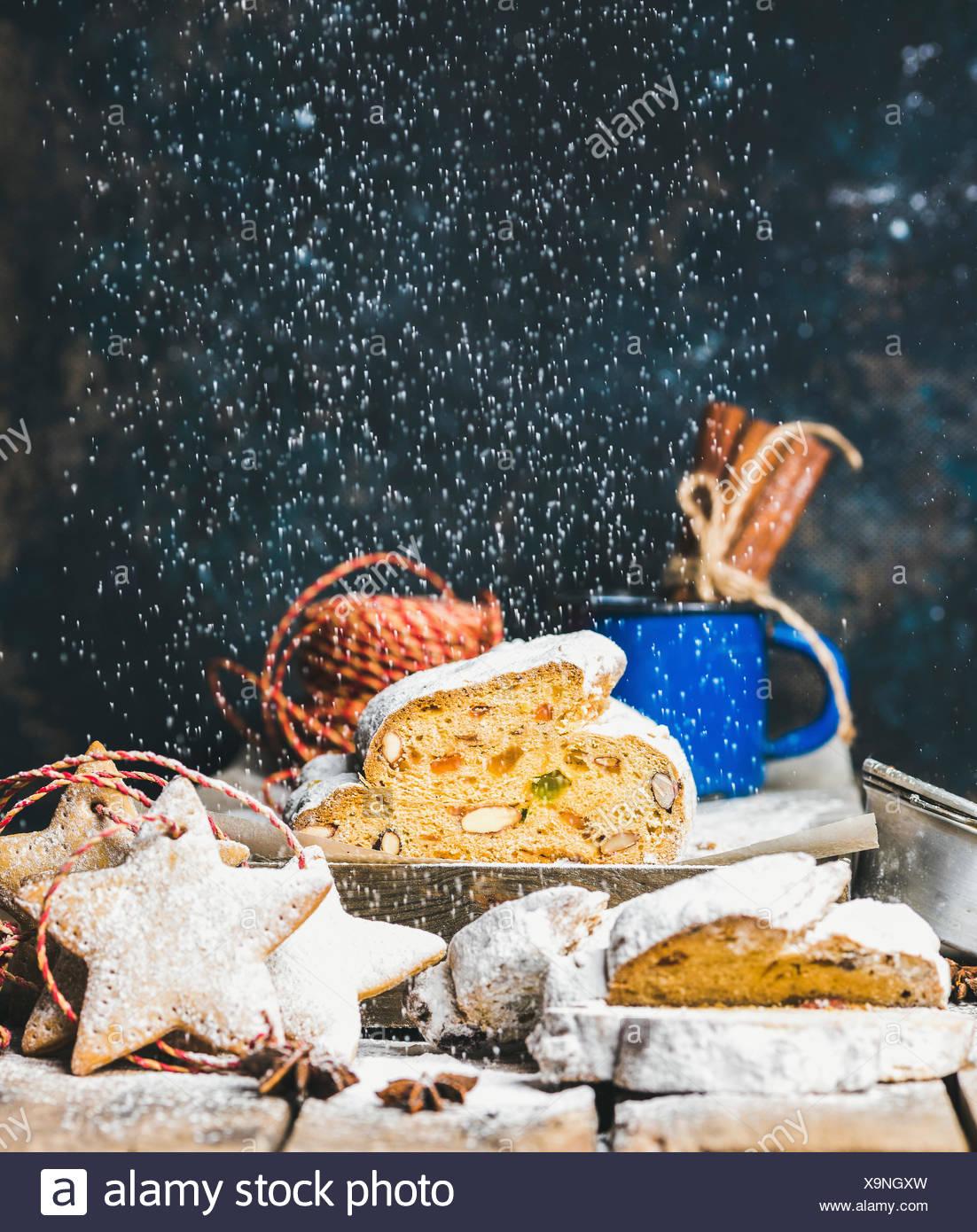 Stück des traditionellen deutschen Weihnachtskuchen Stollen mit festlichen Lebkuchen Sterne geformt, Cookies und fallende Zuckerpuder, Tiefenschärfe, dunkle Blau g Stockbild