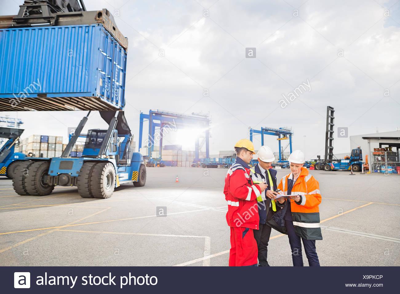 Arbeitnehmer im Frachthafen diskutieren Stockbild