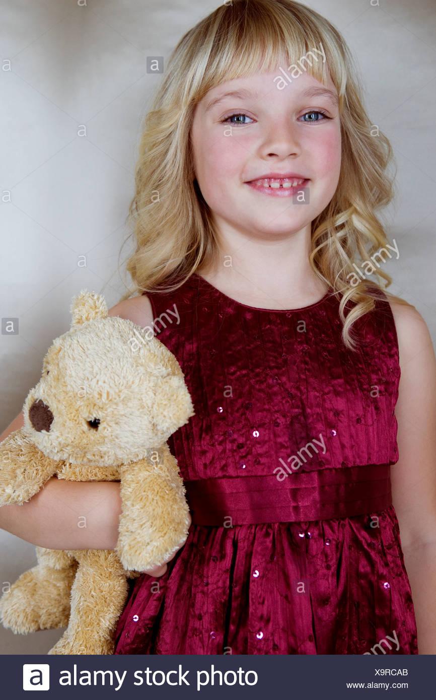 Junges Mädchen im Festkleid, hält einen Teddybär Stockbild