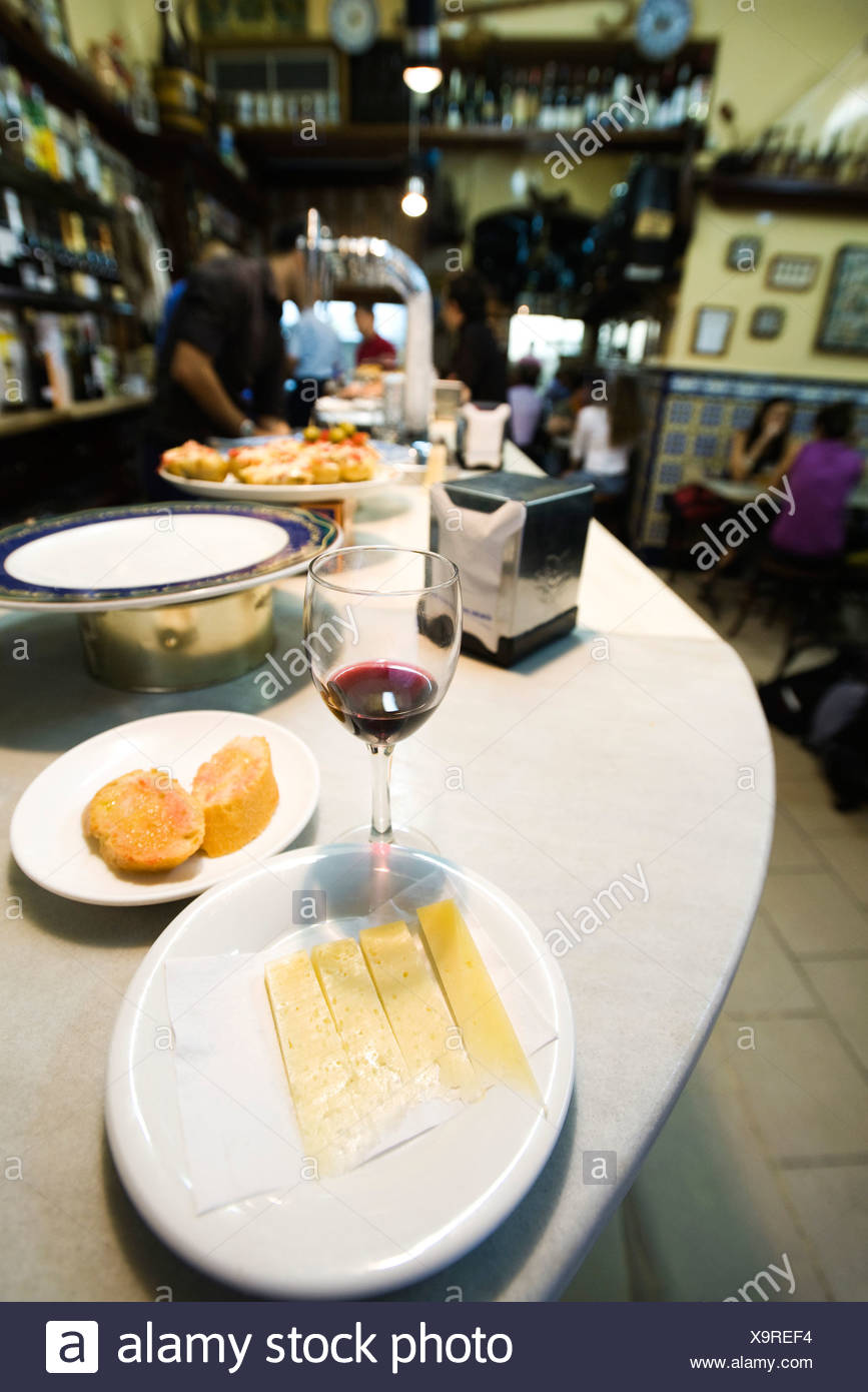 Teller mit Manchego Käse, halbfertigen Glas Wein in der Tapas-bar Stockbild