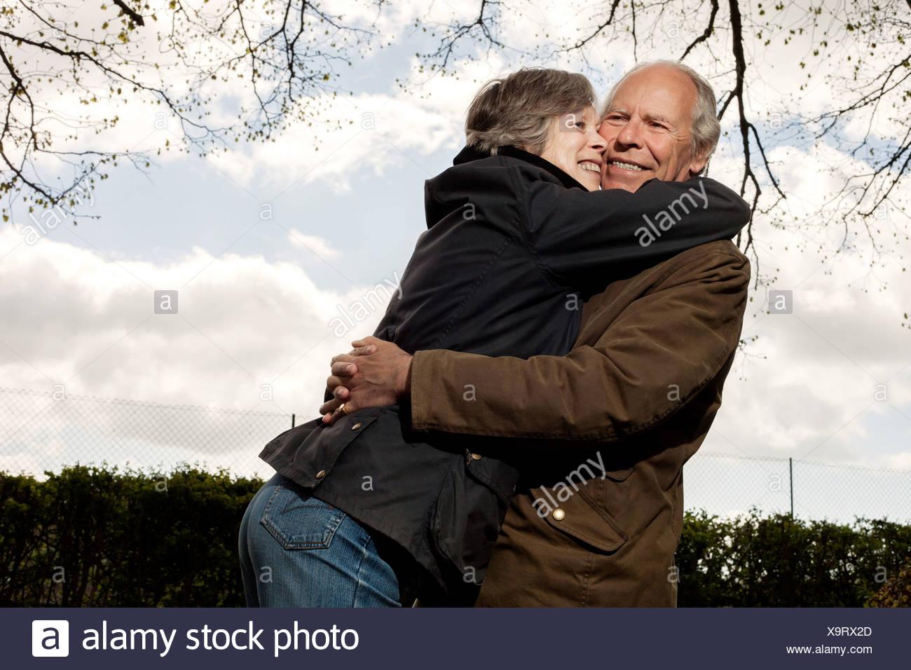Frau umarmt Mann Rundhals-Ausschnitt Stockbild