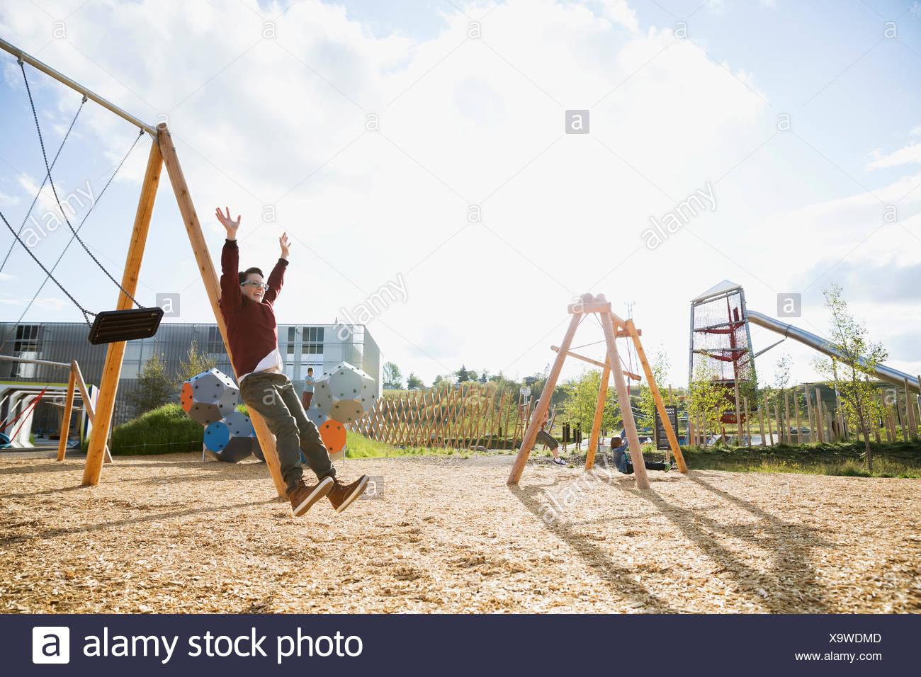Junge, springen von Swing auf sonnigen Spielplatz Stockbild