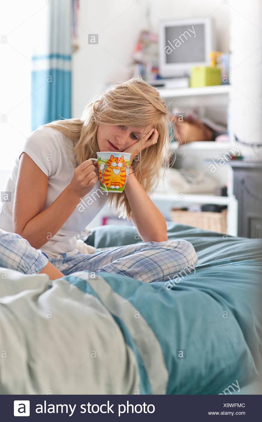 Frau mit Kopf in Händen sitzt auf dem Bett mit Kaffeetasse Stockbild