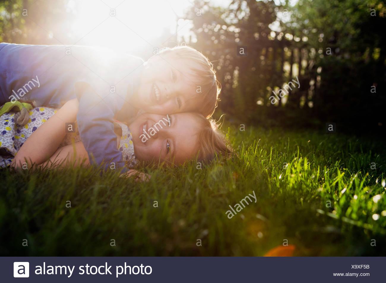 Bruder und Schwester liegen auf dem Rasen, umarmen Stockbild
