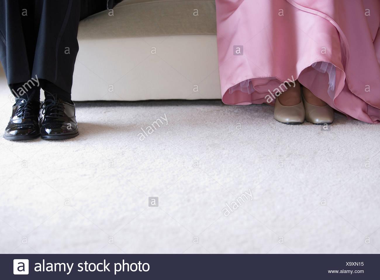 Frau in rosa Kleid, und Mann im Anzug, sitzen an den ...