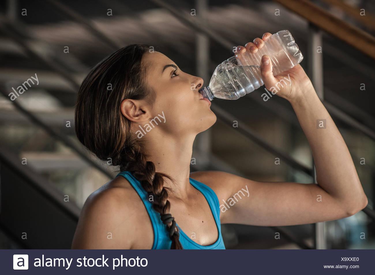 Junge Frau Trinkwasser aus der Flasche Stockbild