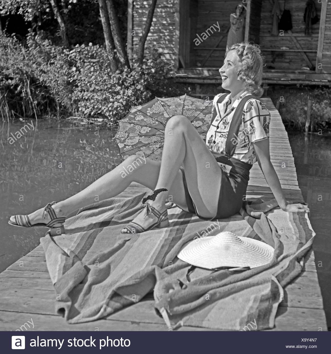 Eine Junge Frau Sitzt im Strandmode Auf Einem Holzsteg ein Einems sehen, 1930er Jahre Deutschland. Eine junge Frau im Strandkleid sitzen auf einem Holzsteg am See, Deutschland der 1930er Jahre. Stockbild