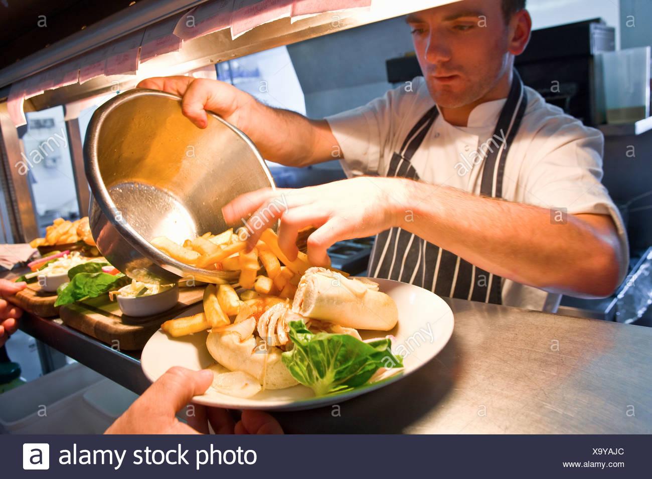 Koch mit Gericht im Restaurantküche Stockbild