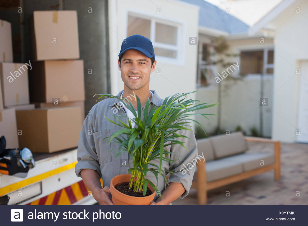 Lächelnd Mann mit Blumentopf Möbelwagen Stockbild