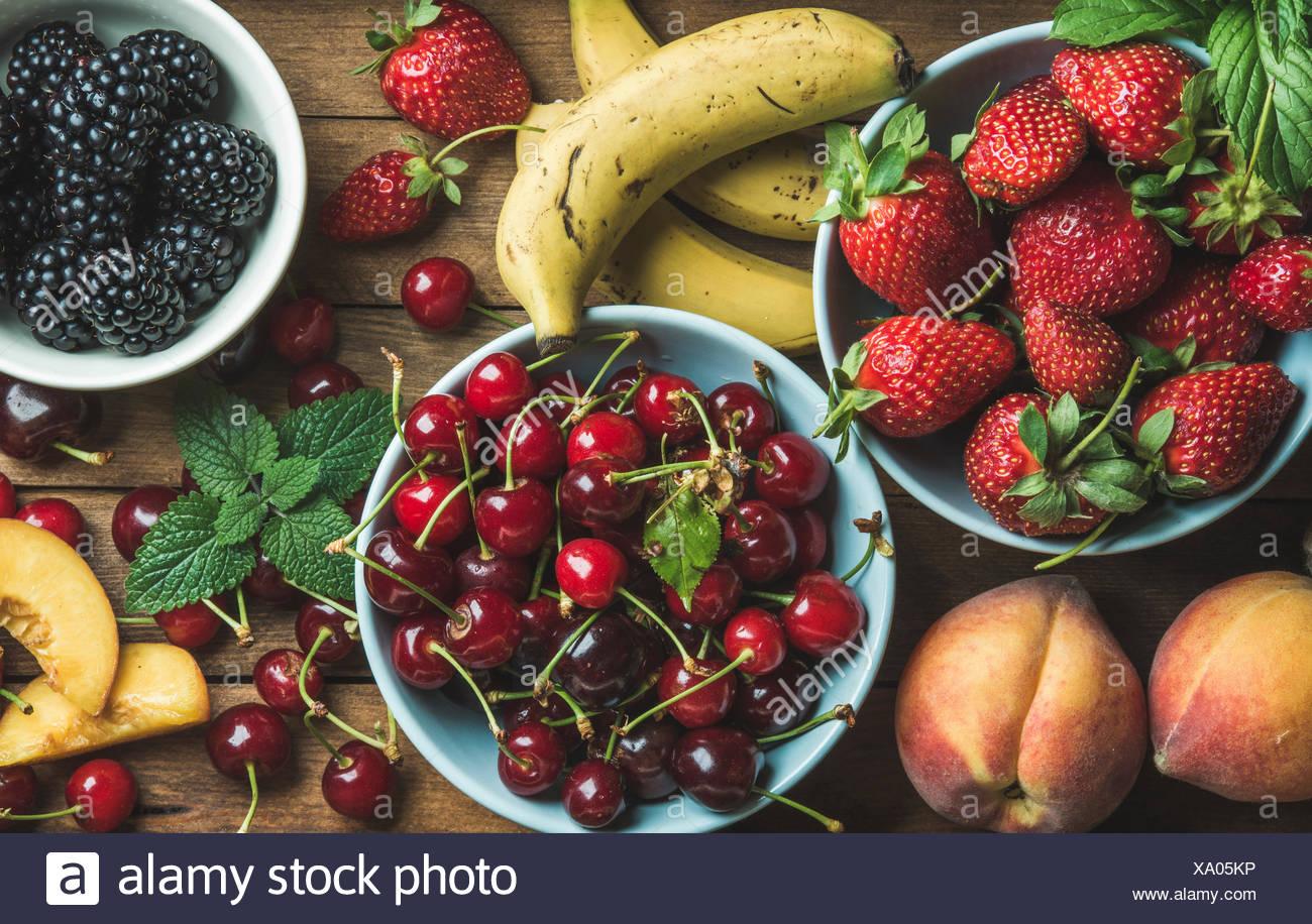 Sommer frische Früchte und Beeren-Vielfalt über hölzerne Kulisse, Draufsicht, horizontale Komposition Stockbild