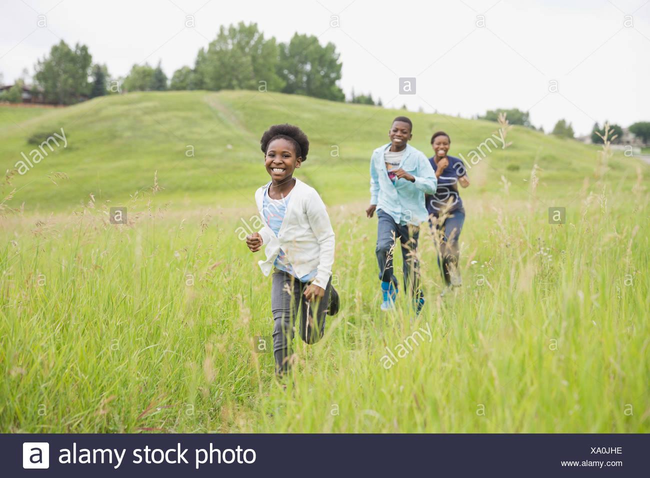 Fröhlichen Geschwister durch Feld Stockbild