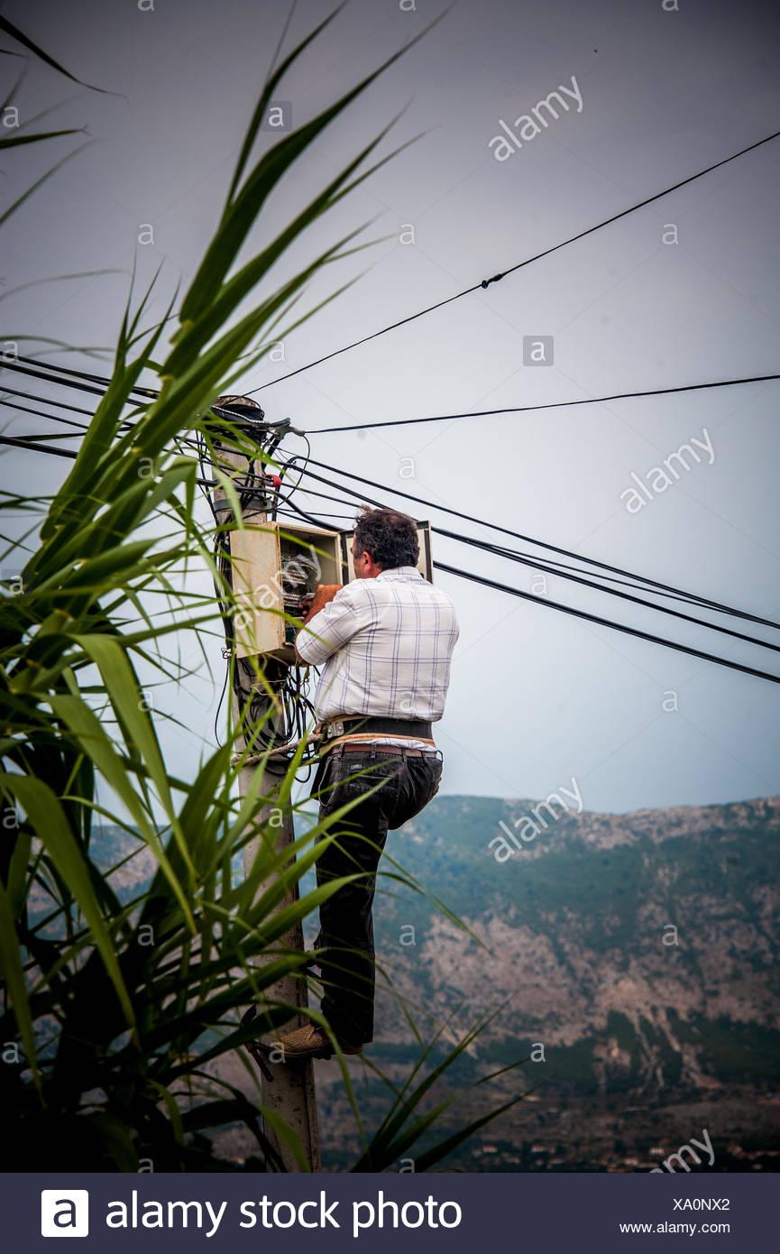 Ein Mann, die Festsetzung einer Strom-Kiste in Albanien. Stockbild