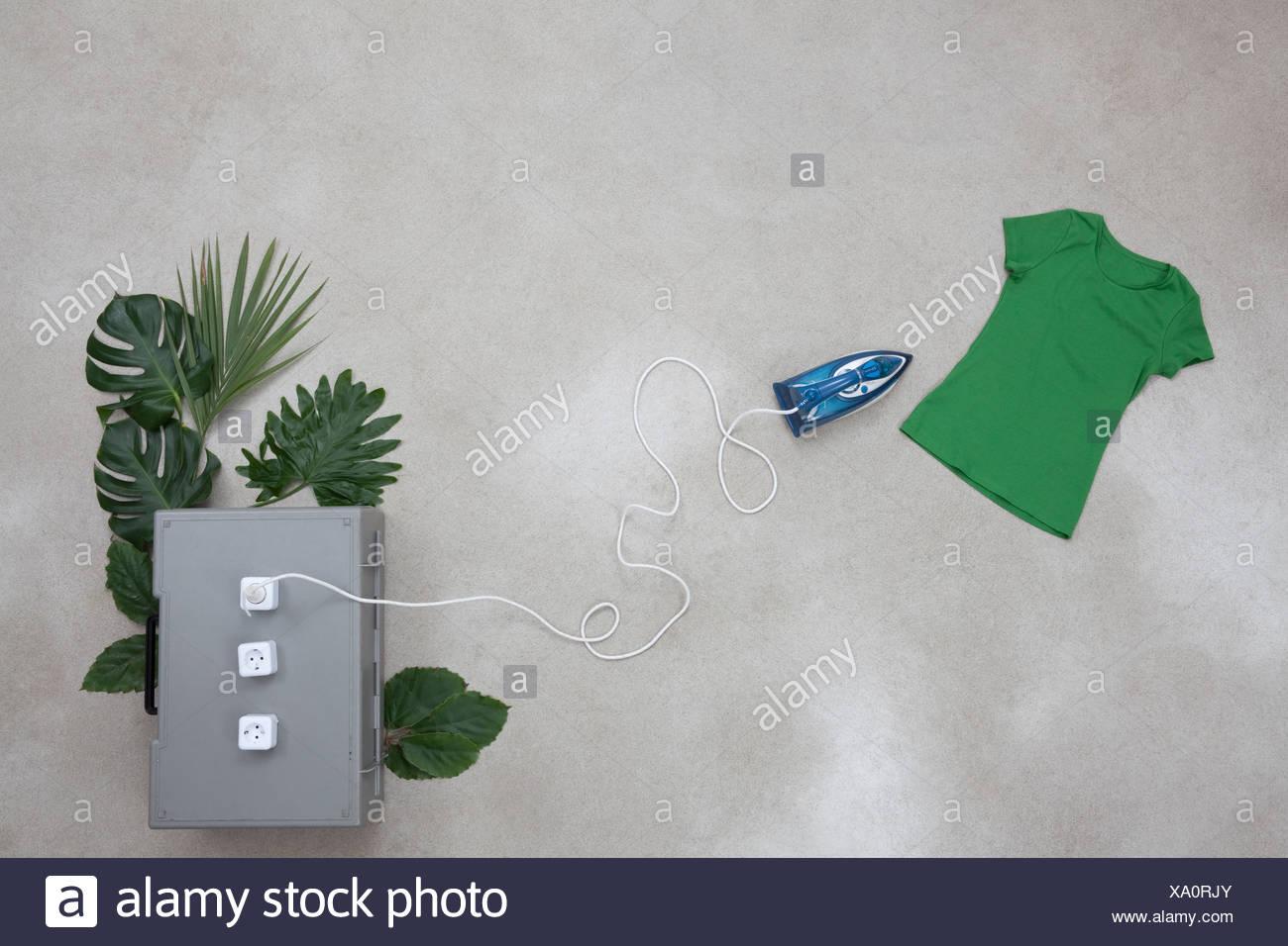 Eisen-Anschluss an Steckdosen mit Blättern, T-shirt auf grauem Hintergrund Stockbild