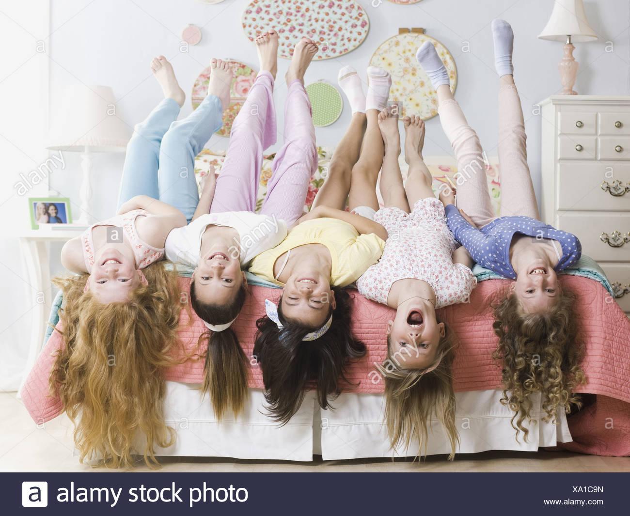 fünf Mädchen auf ein Bett auf den Kopf nach unten Stockbild