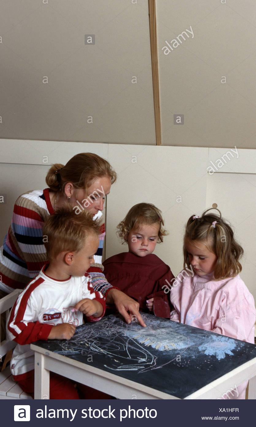 Tagespflege-Einrichtung: Kind Leistungserbringer zeichnen Kreide mit kleinen Kindern im Haus. Stockbild