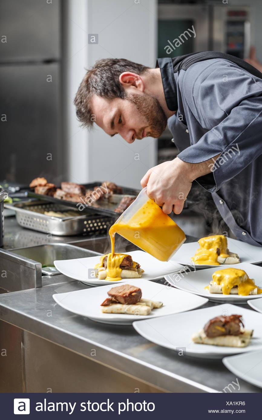 Koch gießt Sauce Stockbild