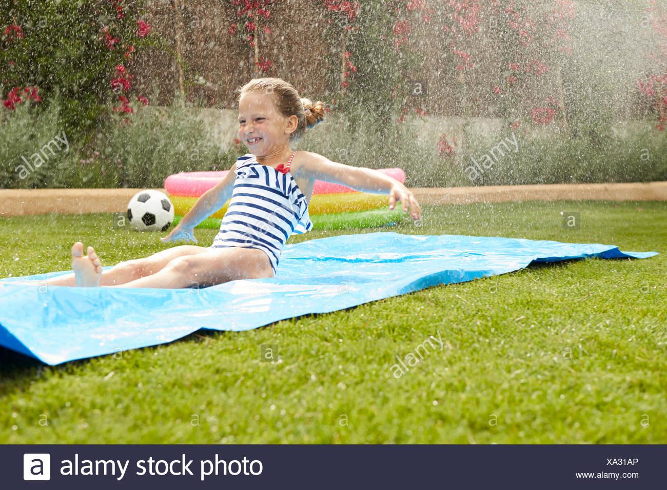 Mädchen Die Spaß Auf Der Wasserrutsche Im Garten Stockfoto Bild