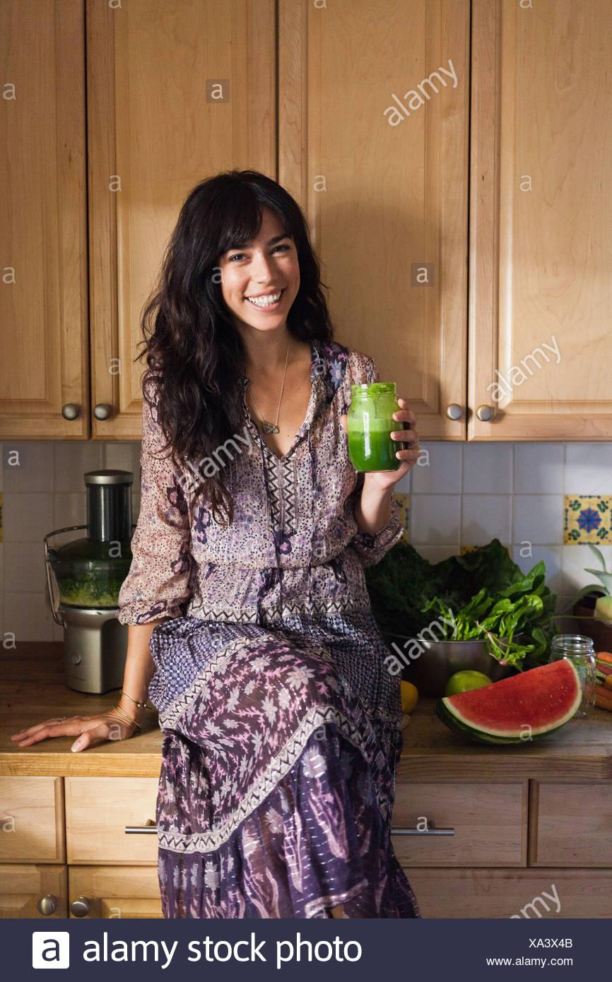 Junge Frau in der Küche mit Gemüsesaft Stockbild