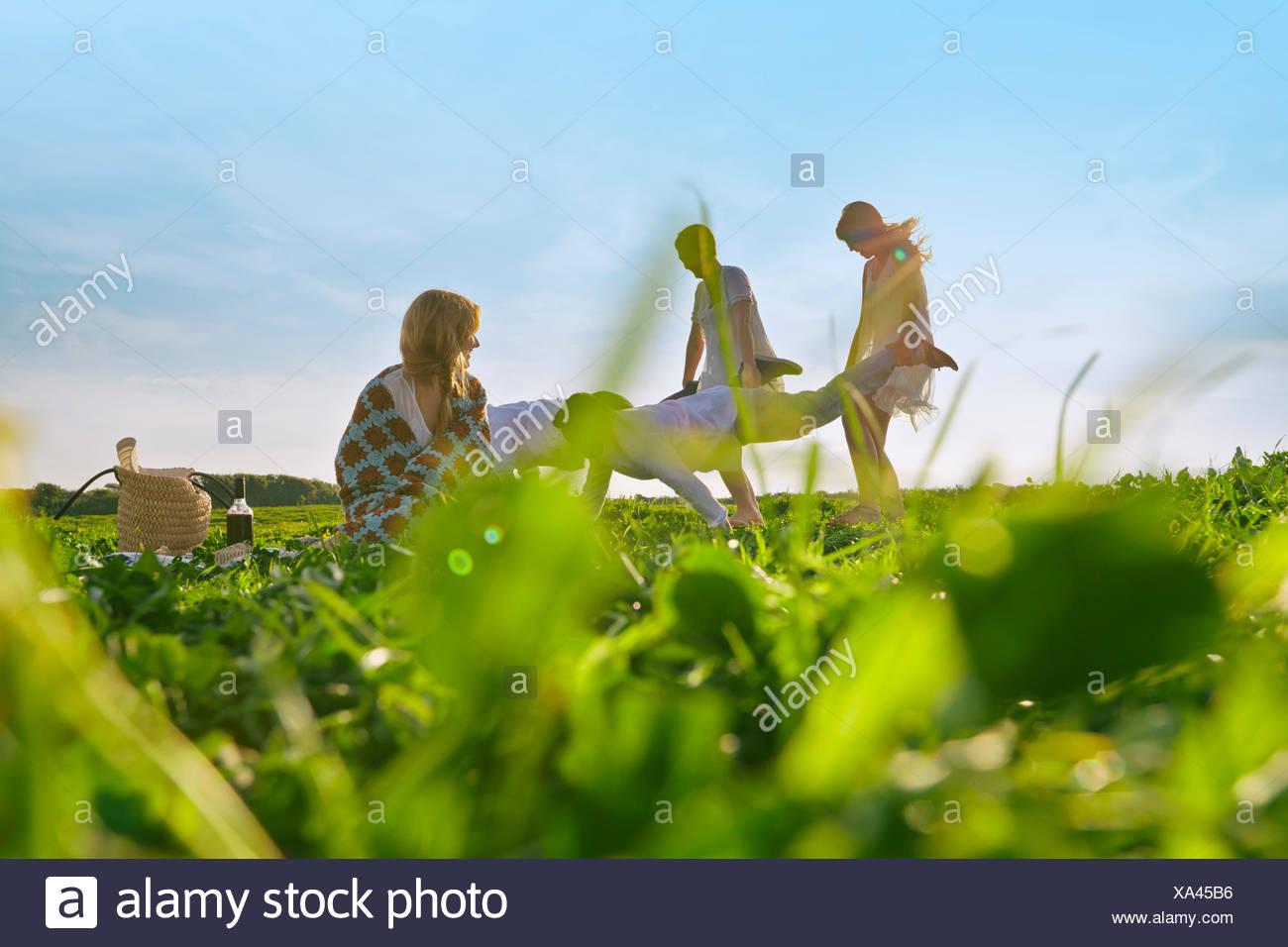 Gruppe von jungen Erwachsenen Freunden vorgeben Schubkarren-Rennen in Feld Stockbild