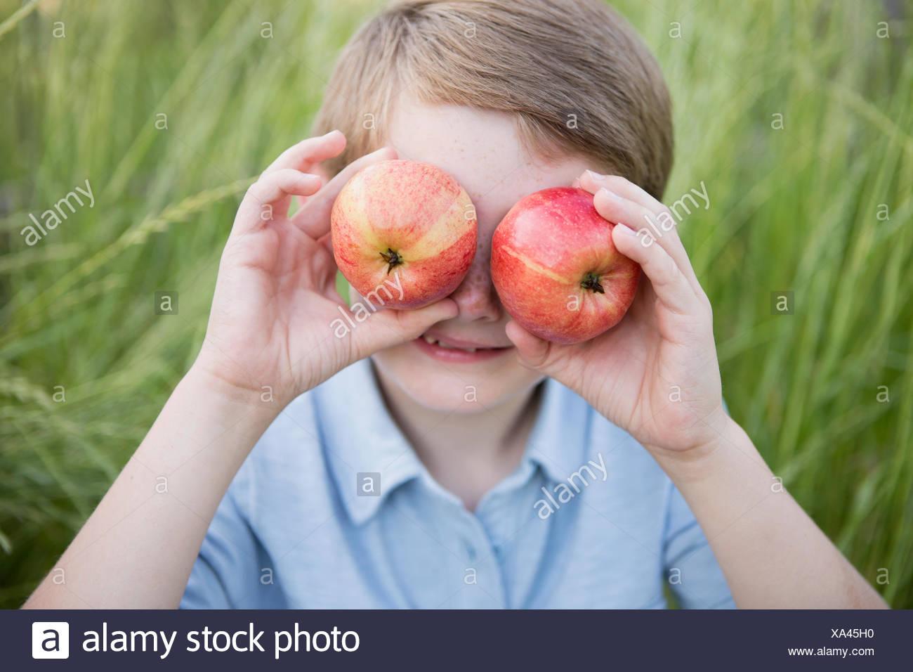 Ein Junge hielt zwei rote gehäutet Äpfel über die Augen. Stockbild