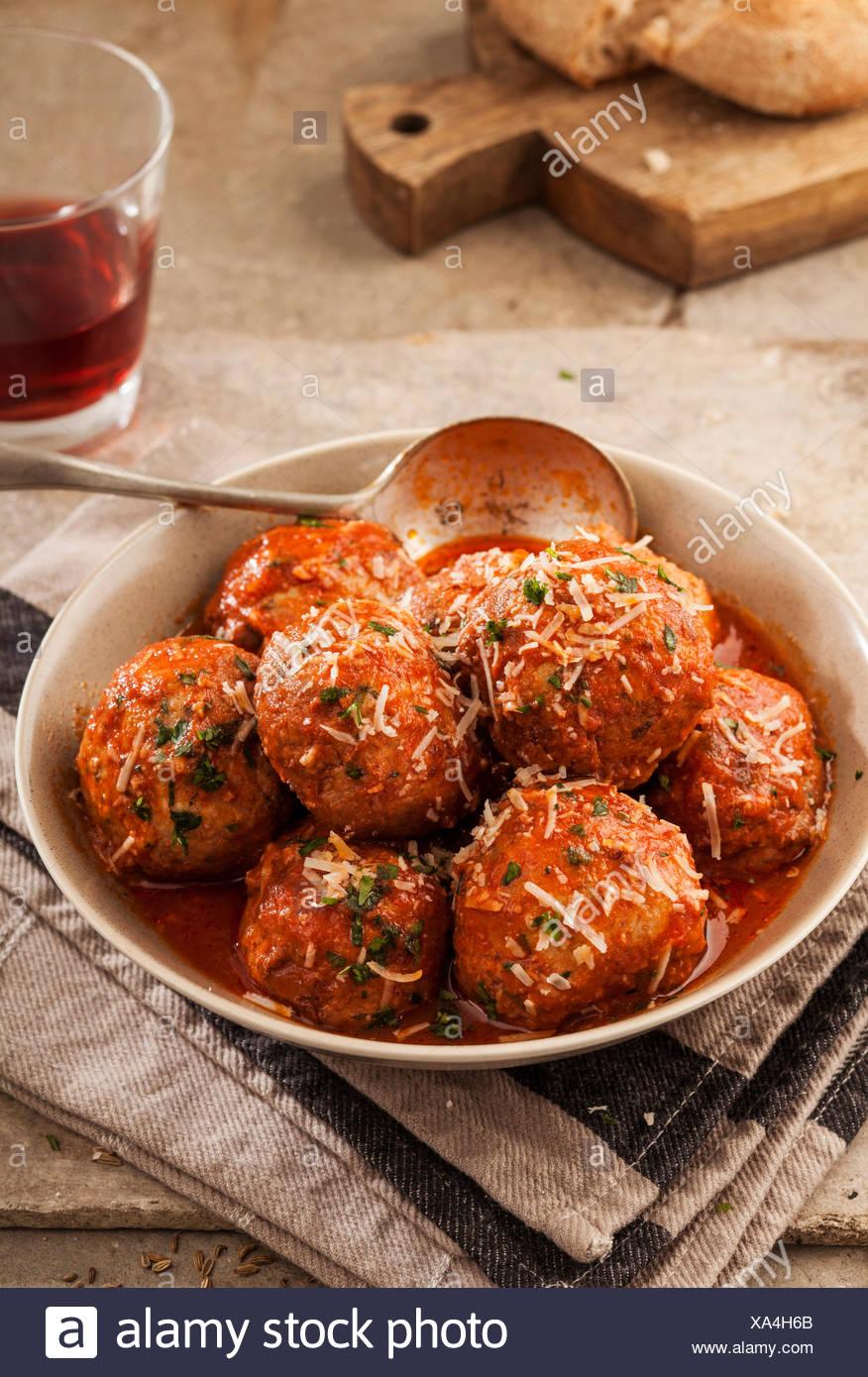 Fleischbällchen in Tomatensauce in Schüssel auf grauem Hintergrund gekocht Stockbild
