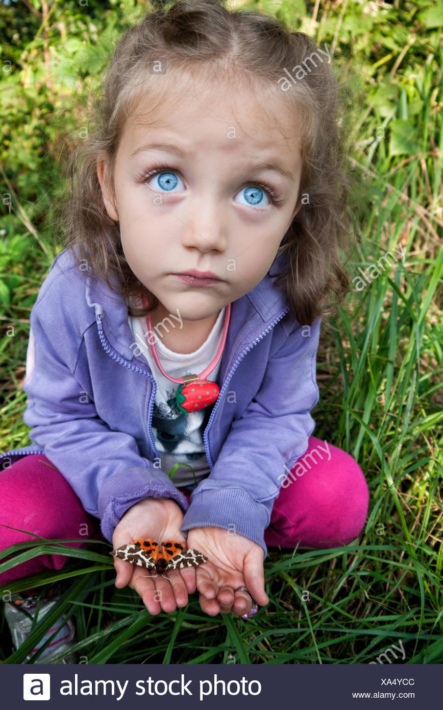 Mädchen hält eine Motte in der Handfläche von ihrer Hand Stockbild