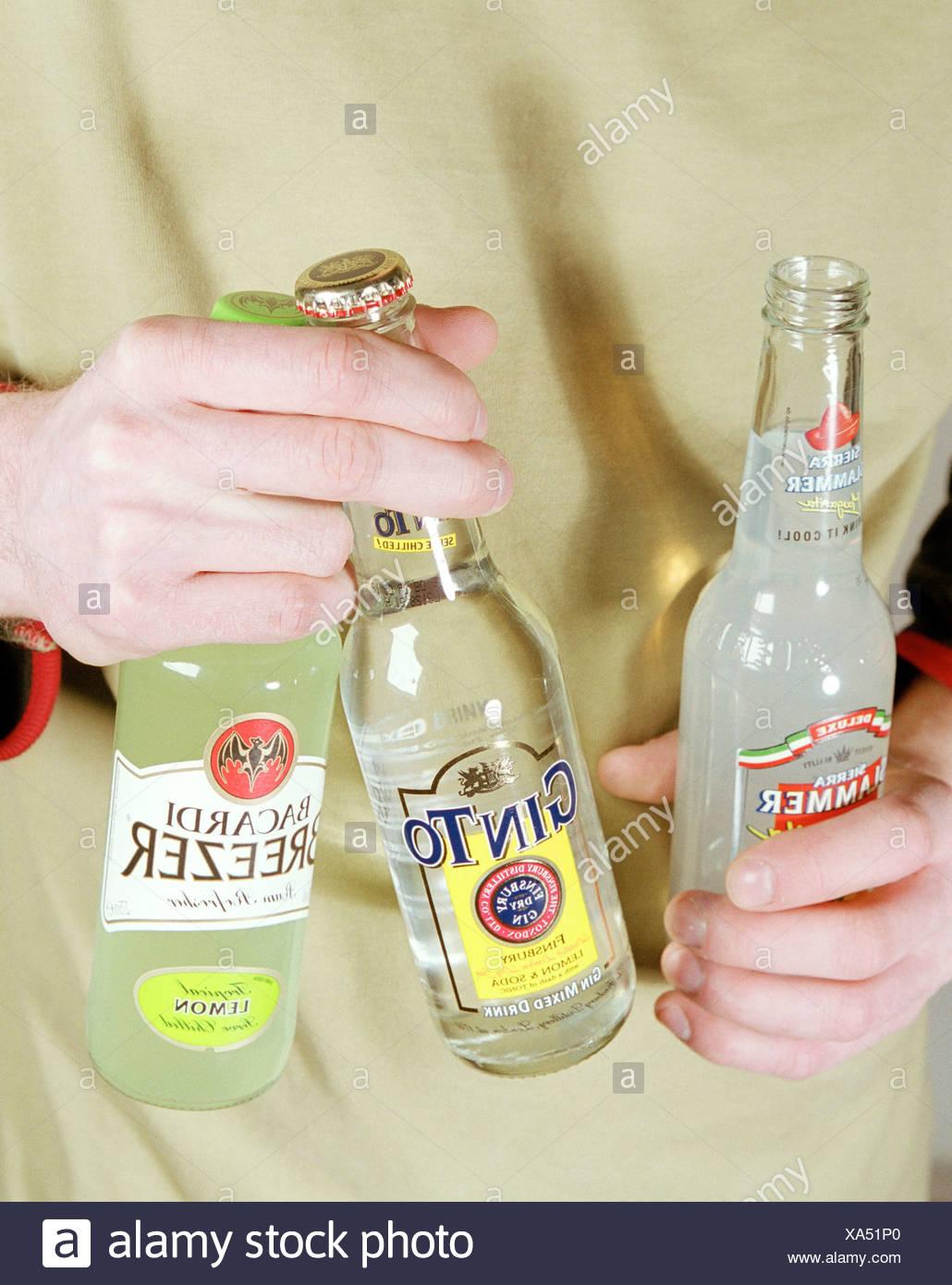 Junger Mann hält mehrere Flaschen alcopops Stockbild