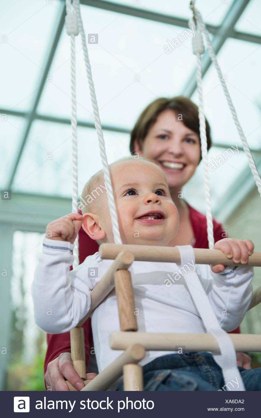 Glücklich Kleinkind sitzt in einem Schwung Stockbild