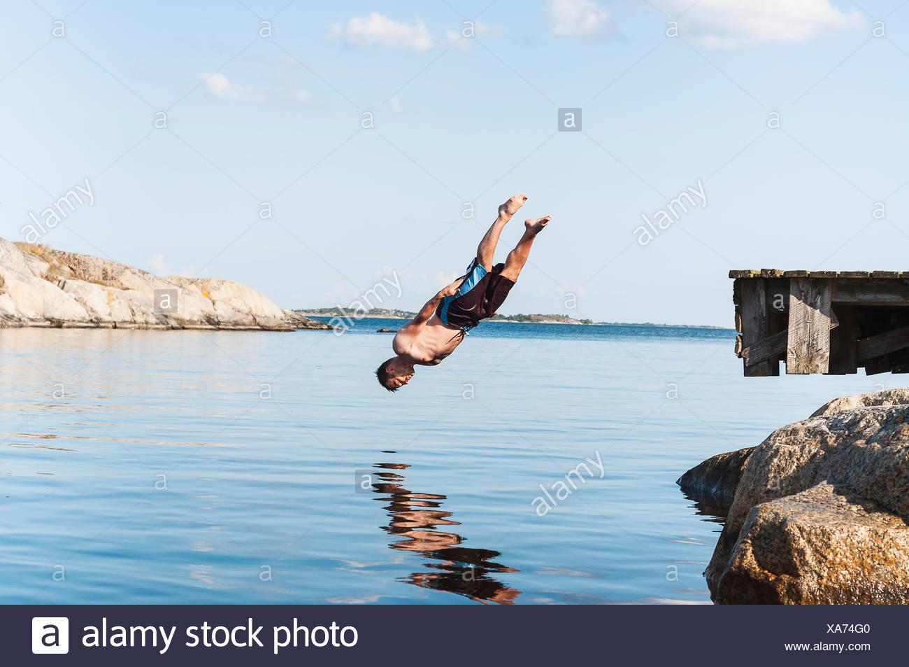 Schweden, Stockholm Archipel, Uppland, Vidinge, Mann springt von der Anlegestelle in See Stockbild