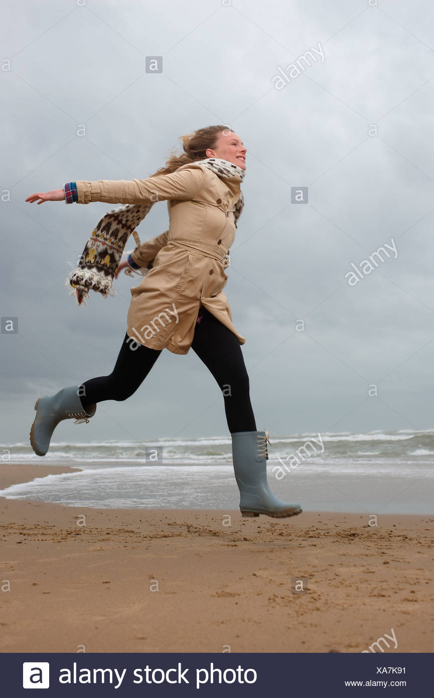 Eine Frau, die entlang einem Strand im Winter Stockbild
