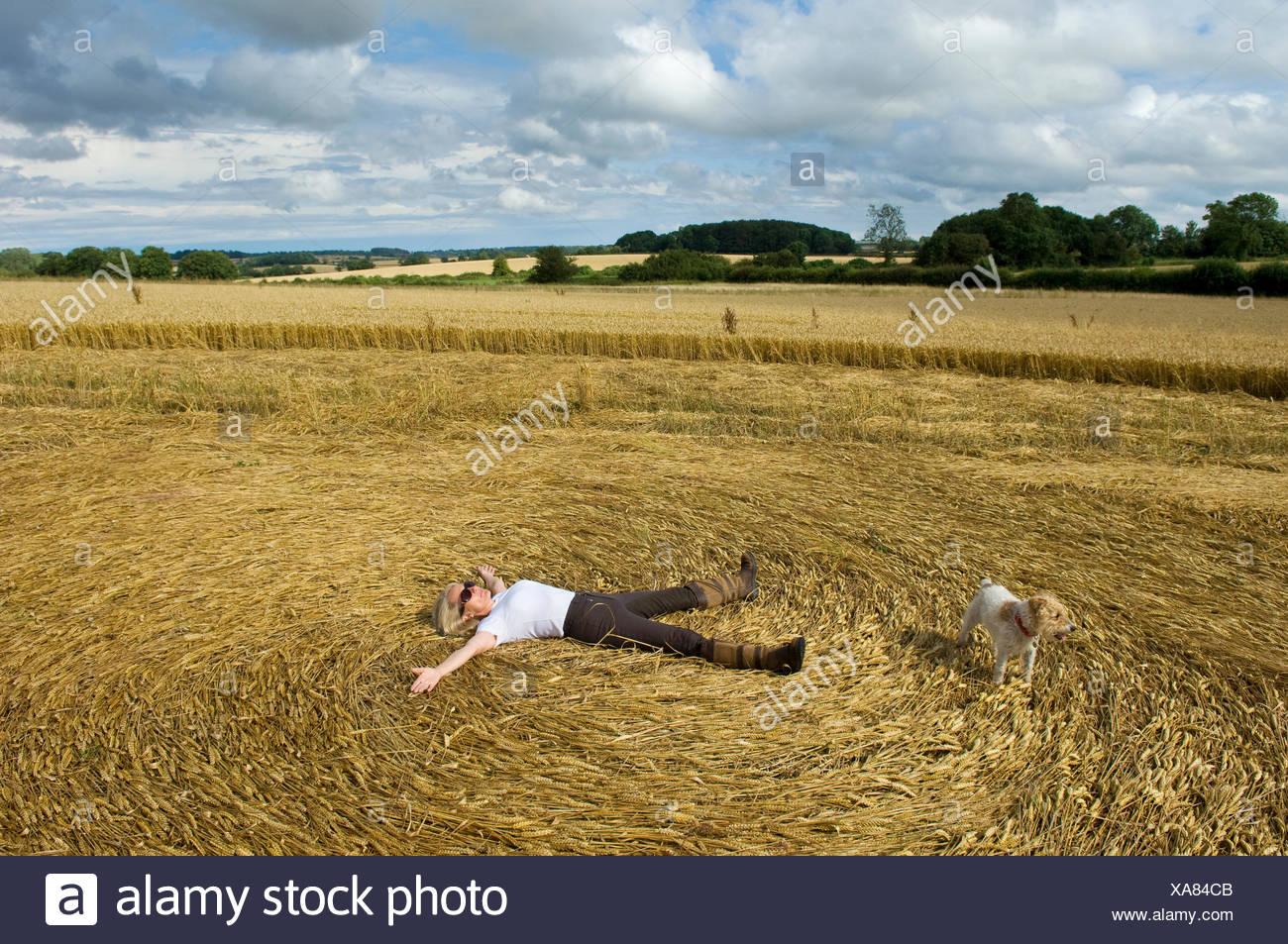 Ein Bauer auf seinem Rücken in die Stoppeln von einem frisch geschnittenen Ernte Feld Erstellen eines Musters im Stroh liegen. Stockbild