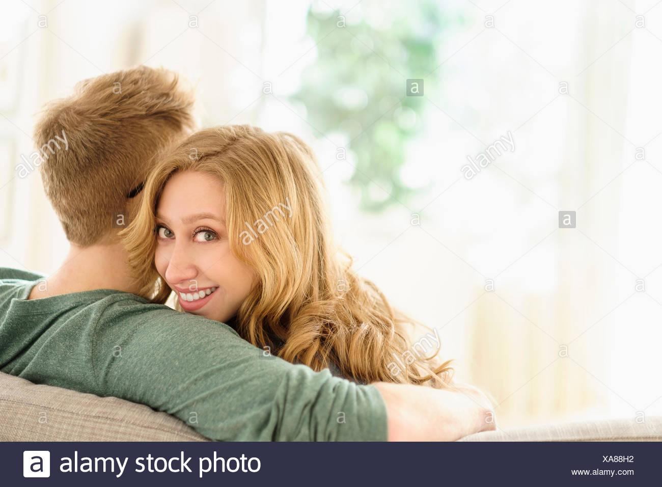 Porträt der jungen Frau umarmt Freund auf sofa Stockbild