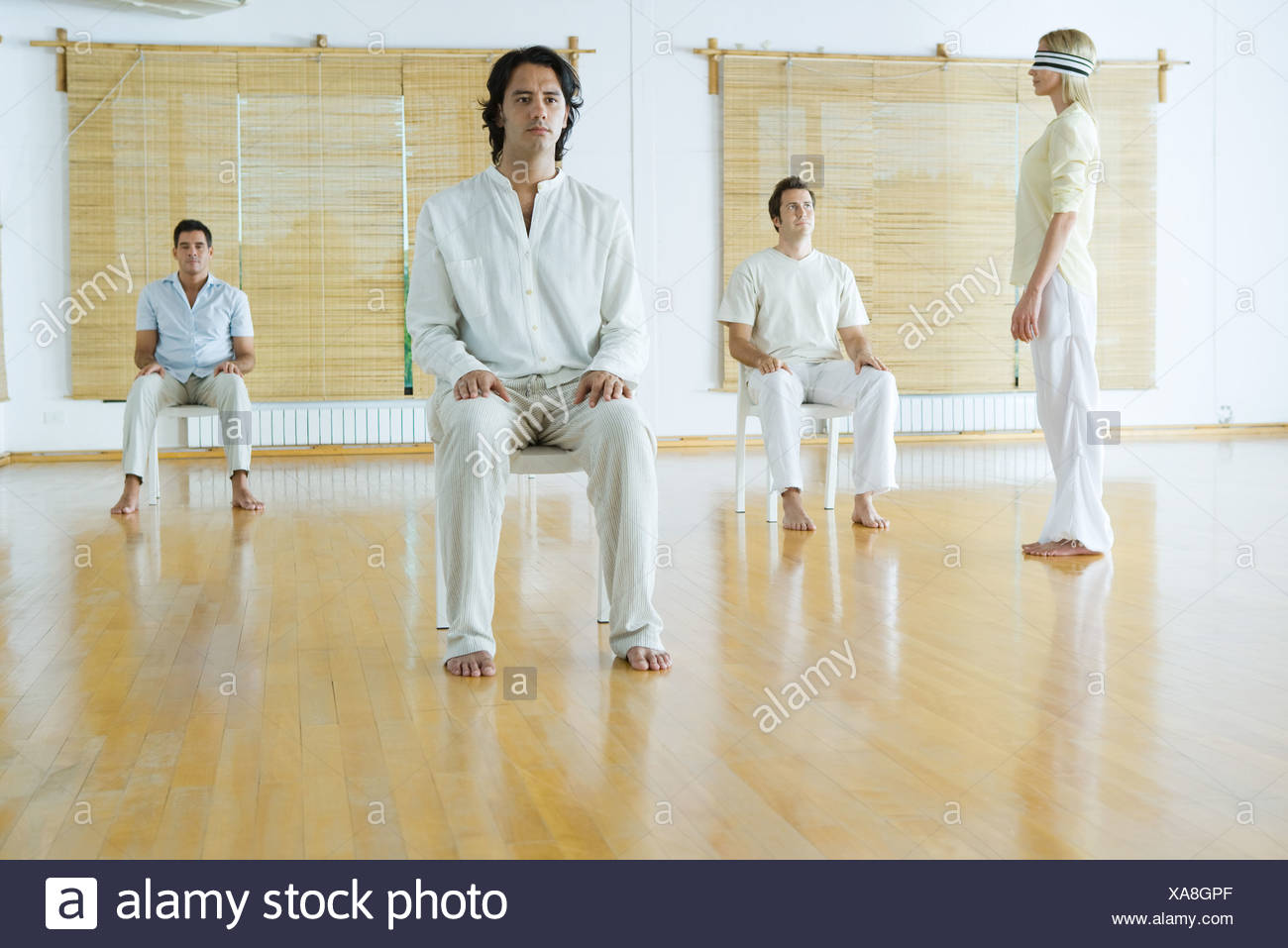 Gruppentherapie, Augenbinde Erwachsene sitzen auf Stühlen, während eine Frau steht, trägt Stockbild